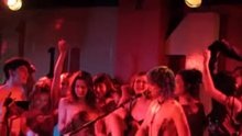 Topless singer and topless audience members.