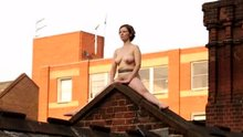 Performance artist naked on the roof